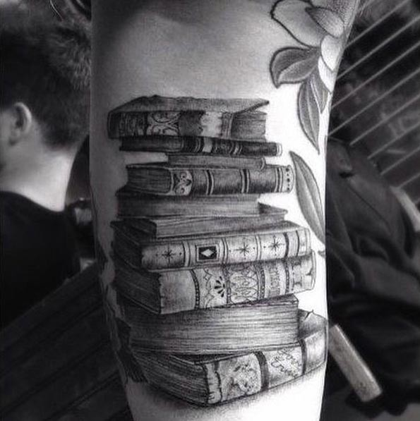 3D like black ink very detailed old magical books tattoo on forearm