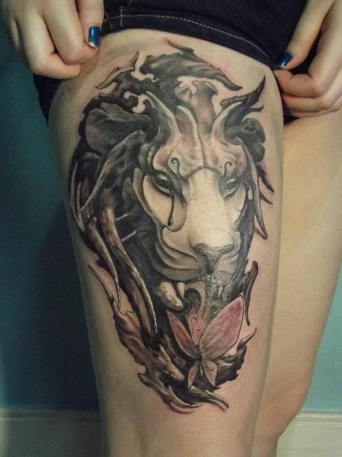 3D like colored demonic lion face tattoo on thigh with butterfly