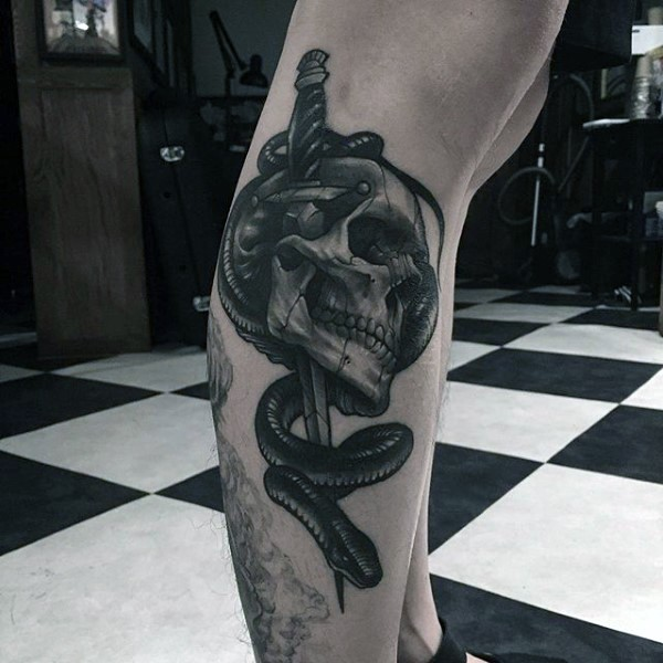 3D like impressive painted colored skull with sword and snake tattoo on leg
