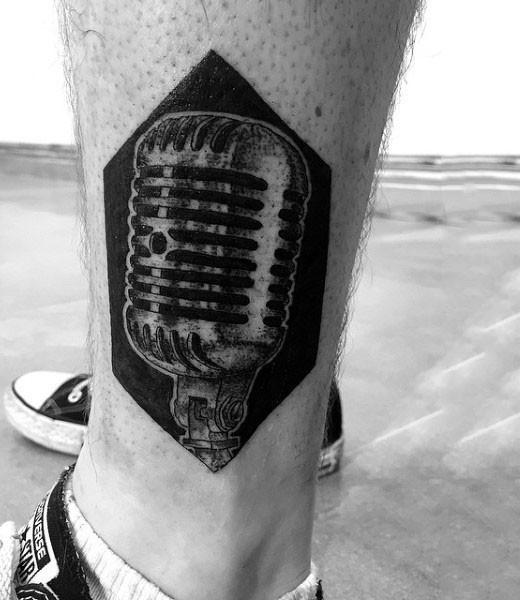 Tatuaje en el tobillo,  micrófono  gris en el fondo negro
