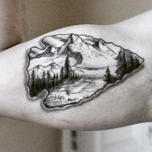 3D like nice colored ancient arrow head tattoo on biceps stylized with mountains and forest