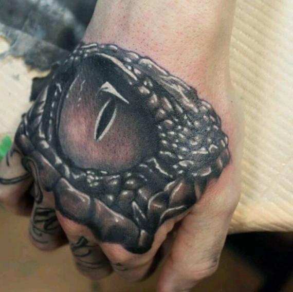 fresco 3D realistico dettagliato occhio di alligatore tatuaggio su mano