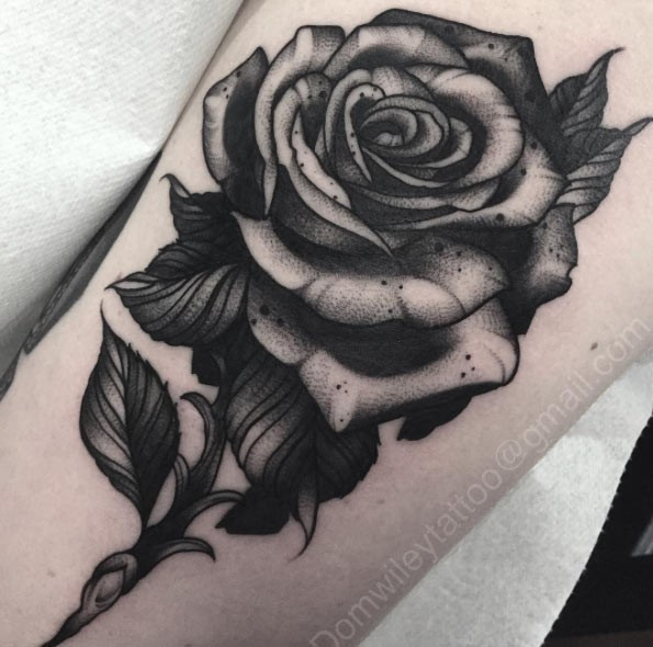 3D style big black ink rose tattoo on forearm