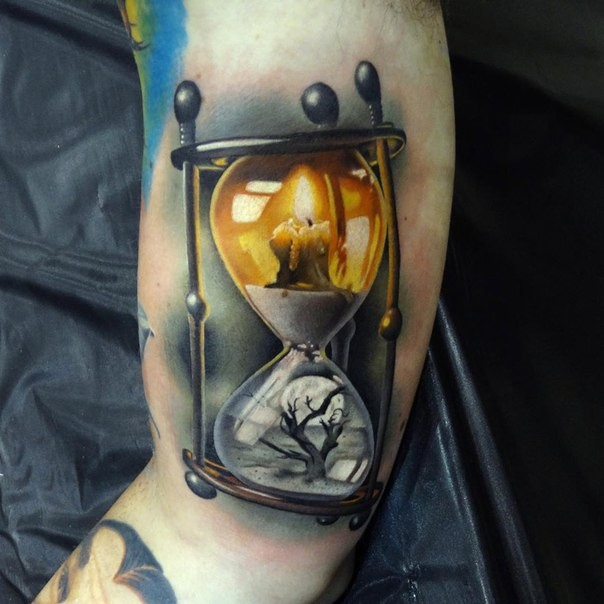 3D style colored biceps tattoo of nice looking sand clock with candle and tree
