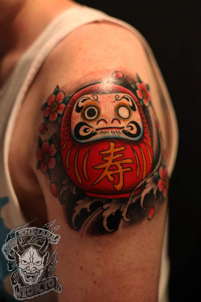 3D style colored shoulder tattoo of small daruma doll with flowers