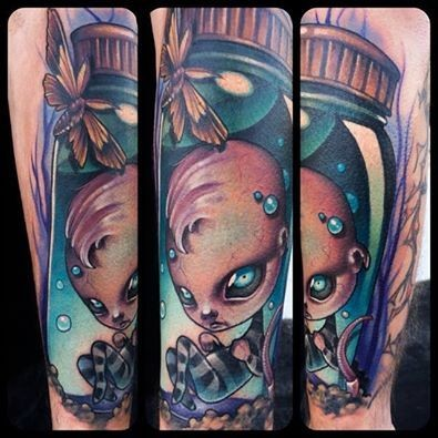3D style colorful forearm tattoo of creepy doll boy with butterfly