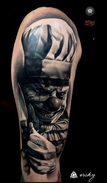 3D style creepy looking shoulder tattoo of maniac clown with knife