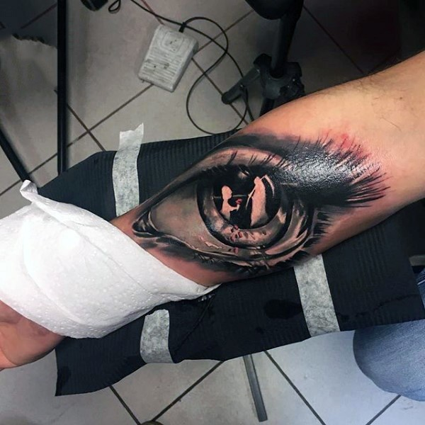 3D style large colored forearm tattoo of human eye stylizedw ith death