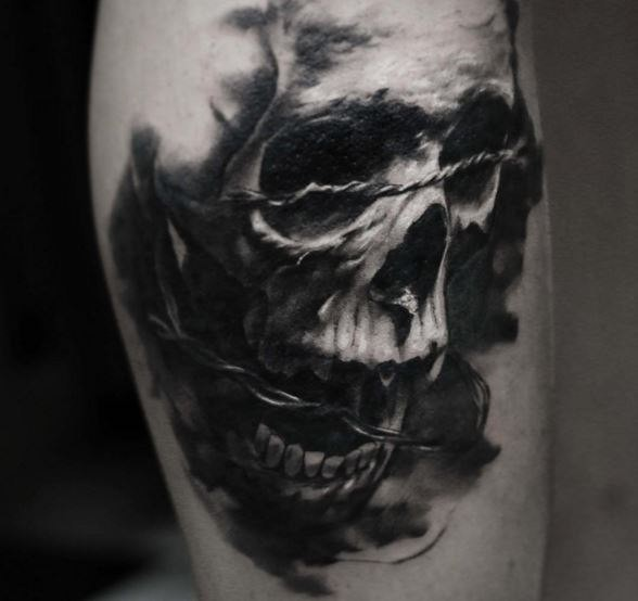 3D style very detailed arm tattoo of human skull with barbed wire