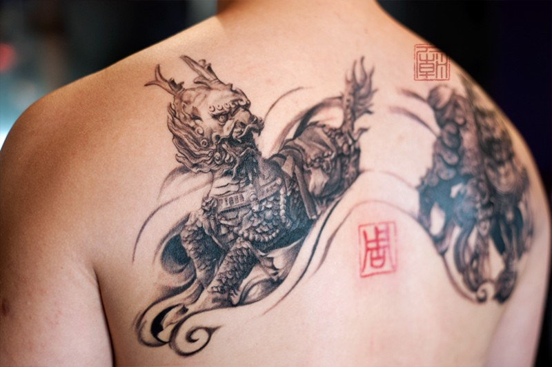 3D style very detailed black and white Asian demons tattoo on upper back combined with tiny red symbol