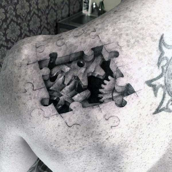3D style very detailed black ink puzzle peaces with old mechanism tattoo on shoulder