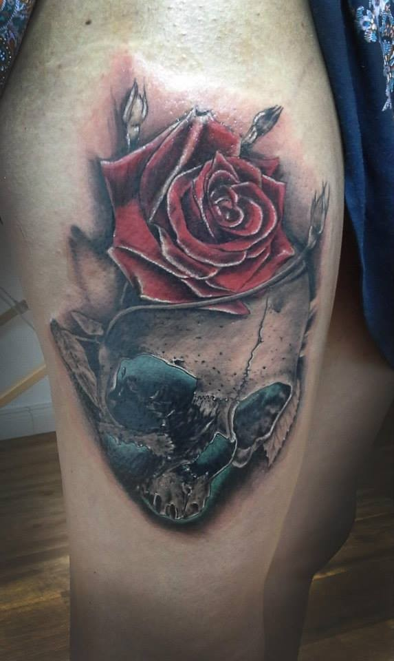 3D style very detailed thigh tattoo of human skull with rose
