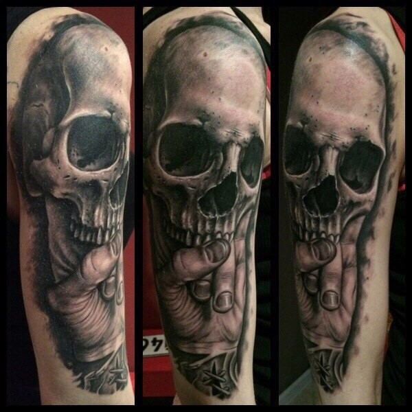 3D very realistic looking black ink half sleeve tattoo of hand holding old skull