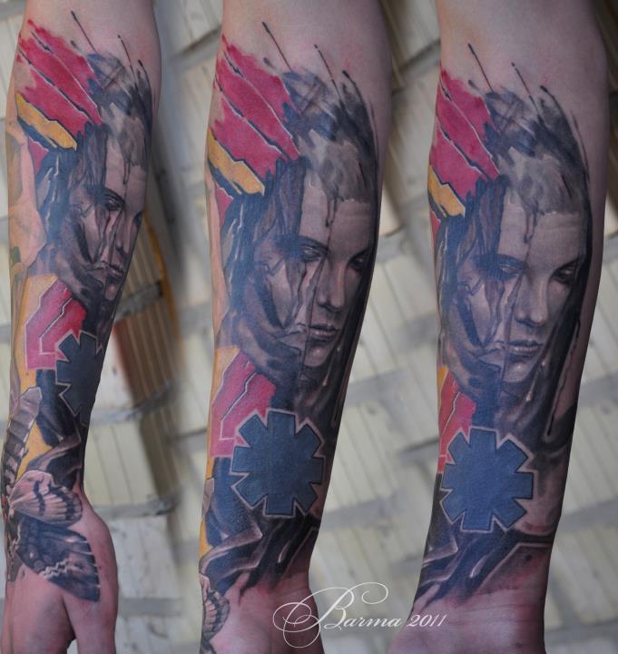 Tatuaggio astratto con volto umano e falena sull&quotavambraccio
