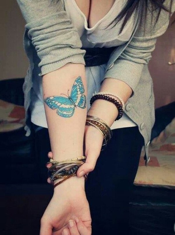Amazing girly blue-colored butterfly tattoo on forearm