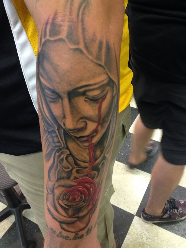 Amazing religious bleeding-eye Virgin Mary tattoo on forearm