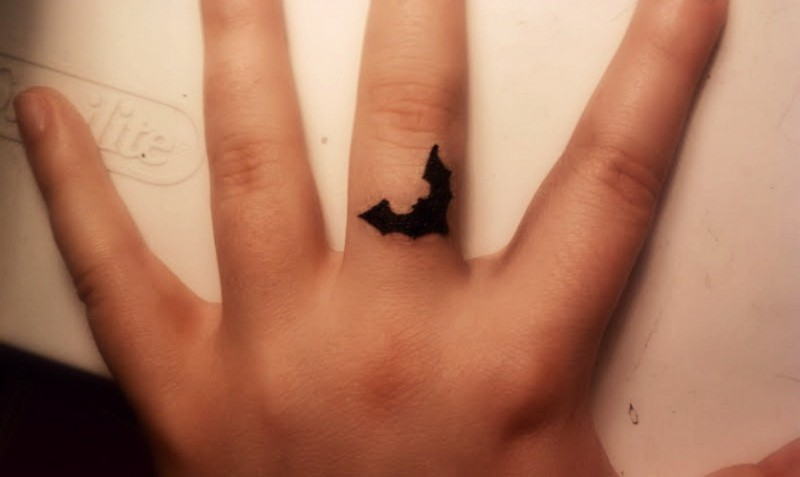 Amazing small black bat tattoo on finger