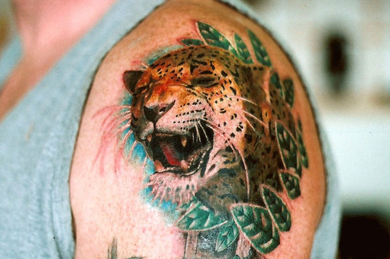 Angry colorful gnarling cheetah in leaves tattoo on shoulder