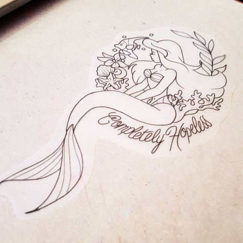 Animated outline ariel mermaid with weeds and lettering tattoo design