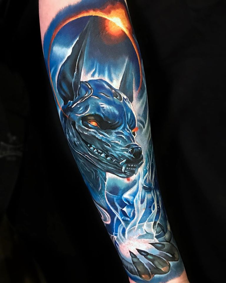 Anubis and space tattoo on arm