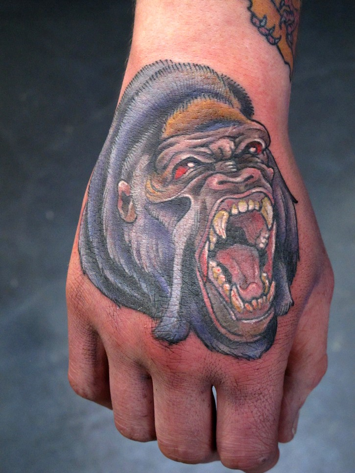 Awesome crying colorful gorilla head tattoo on hand