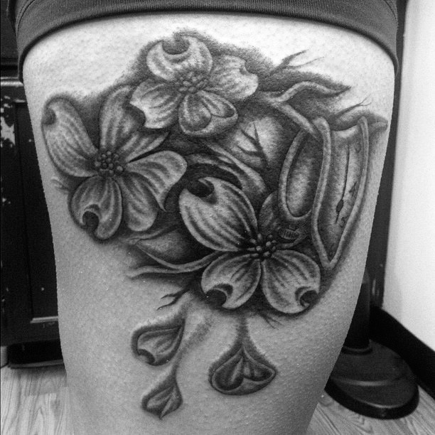 Awesome dark-colored flowers tattoo on thigh