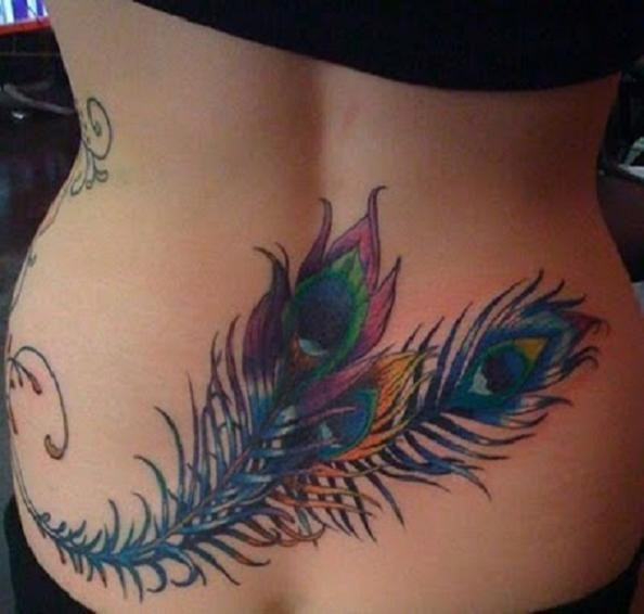 Awesome fuzzy peacock feathers tattoo on lower back