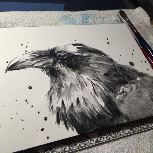 Awesome raven face in black splashes tattoo design