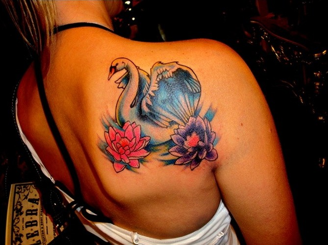 Awesome white swan and colorful lotus flowers tattoo on upper back