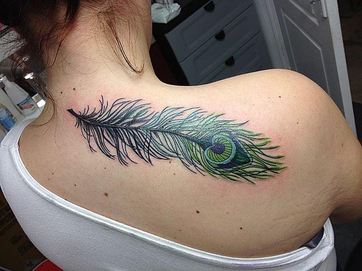 Beautiful green peacock feather tattoo on back