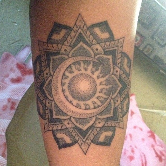 Beautiful mandala flower with sun and moon tattoo on arm