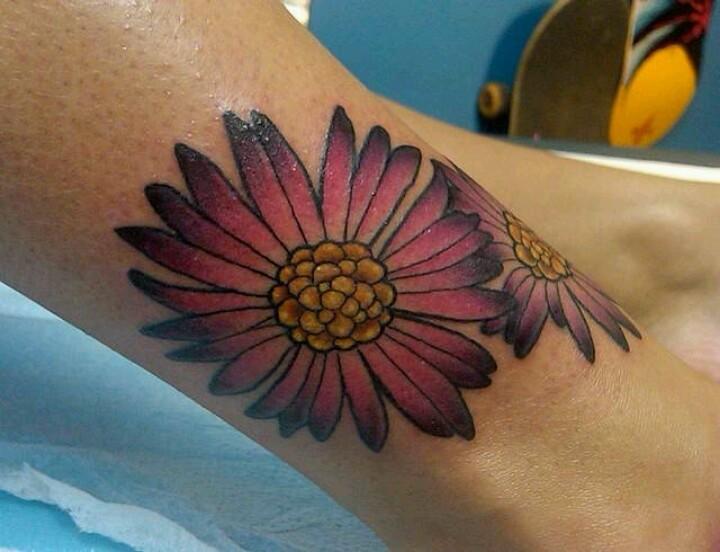 Beautiful pink aster flower tattoo on leg