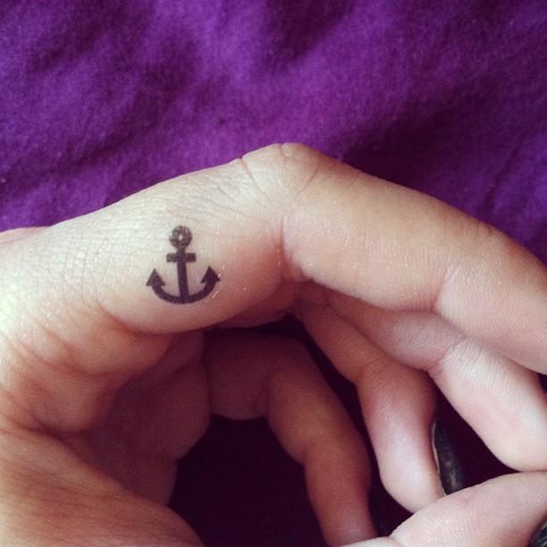 Tatuaje  de ancla simple negra en el dedo
