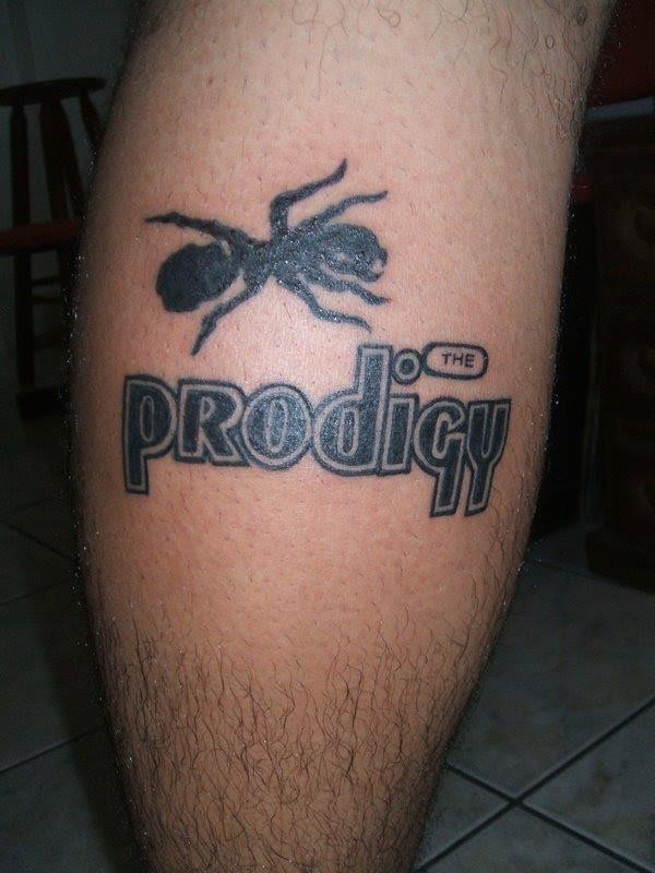 Big black-ink ant with prodigy quote tattoo on shin