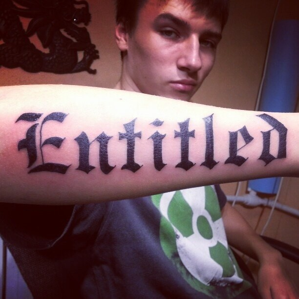 Big imposing entitled quote tattoo for men on arm
