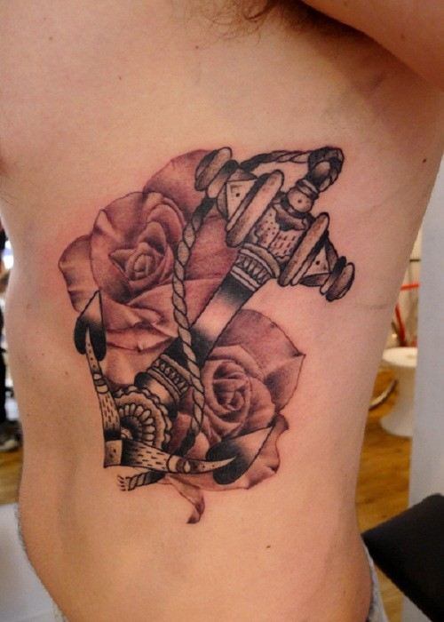 Black-and-white anchor in pale roses tattoo on rib-side