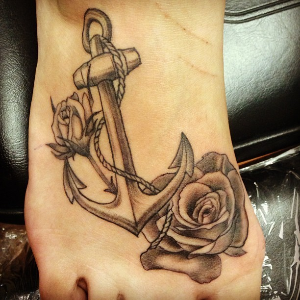 Black-and-white anchor with dreadful roses tattoo on foot
