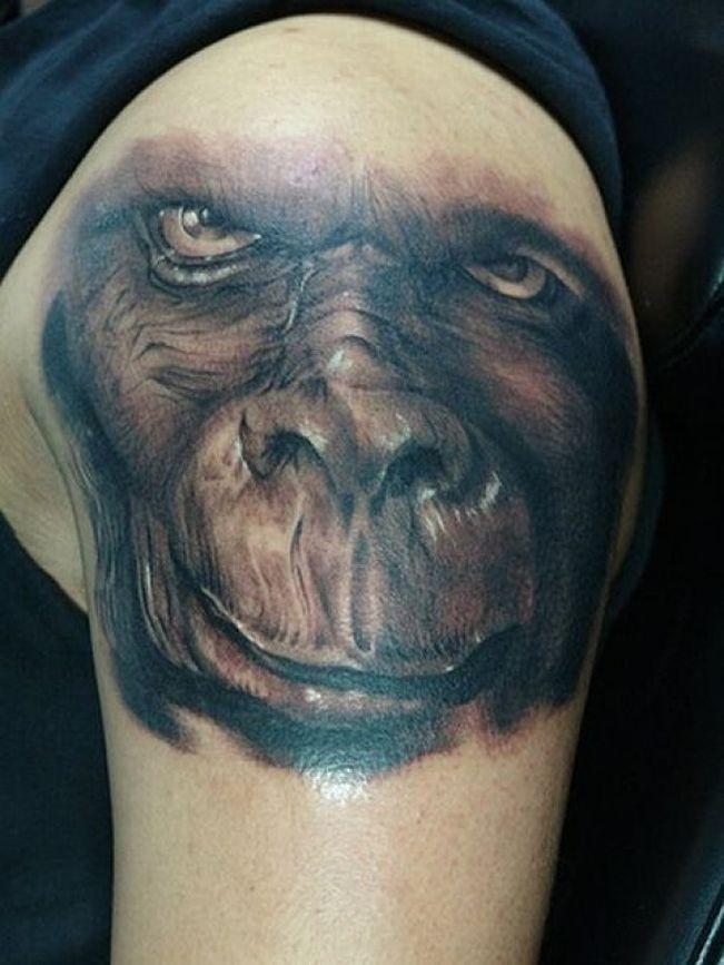 Black-and-white gorilla muzzle tattoo on upper arm