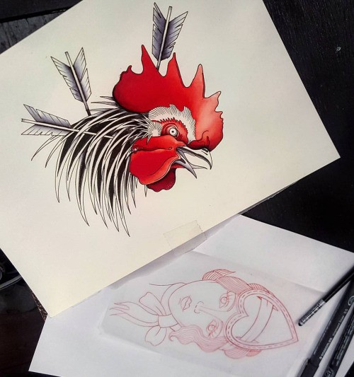 Black-feathered rooster head with red topknot killed with arrows tattoo design