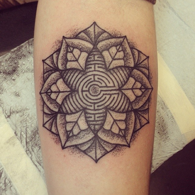 Black-ink mandala flower with labyrinth tattoo on arm