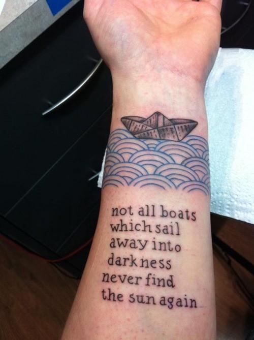 citazione lettere nere con barca di carta su onde blu tatuaggio su polso