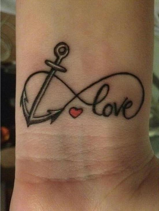 Black anchor infinity with love lettering and tiny red heart tattoo on wrist