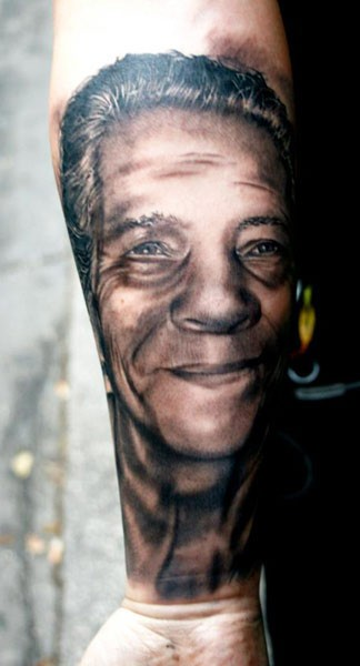 Black and gray style detailed forearm tattoo of old man face