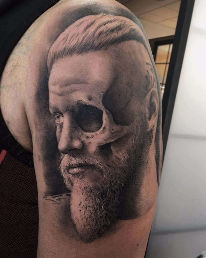Black grey arm tattoo of half human skull with viking