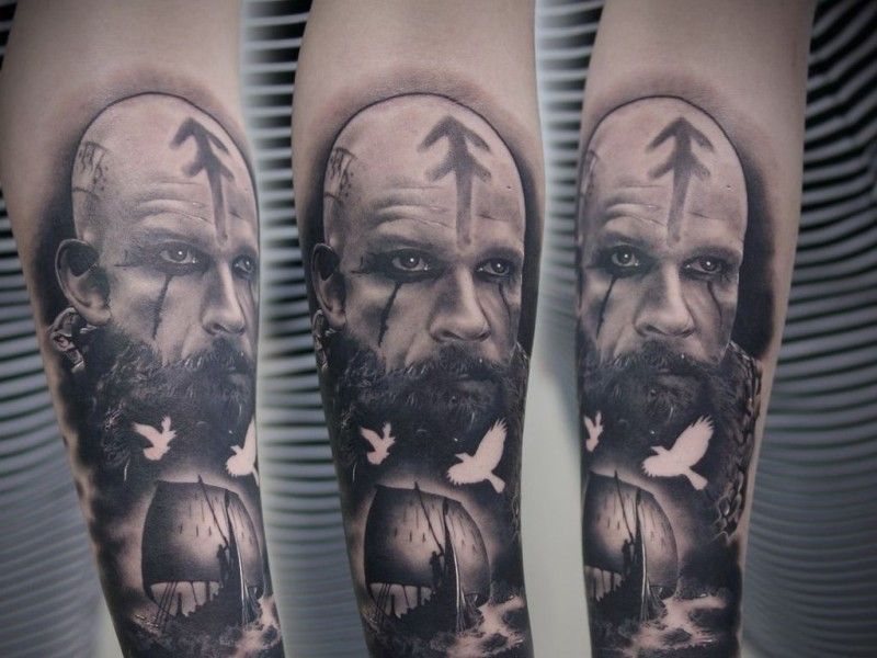 Black grey portrait of viking with ship tattoo