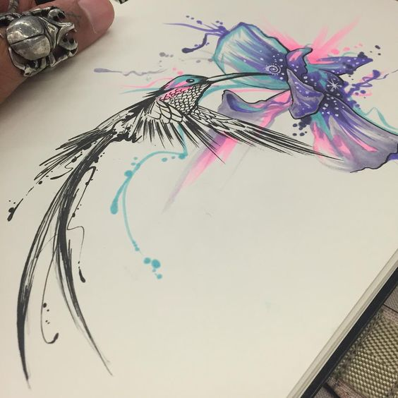 Black hummingbird sniffing pink-and-purple hibiscus flower with watercolor effect tattoo design