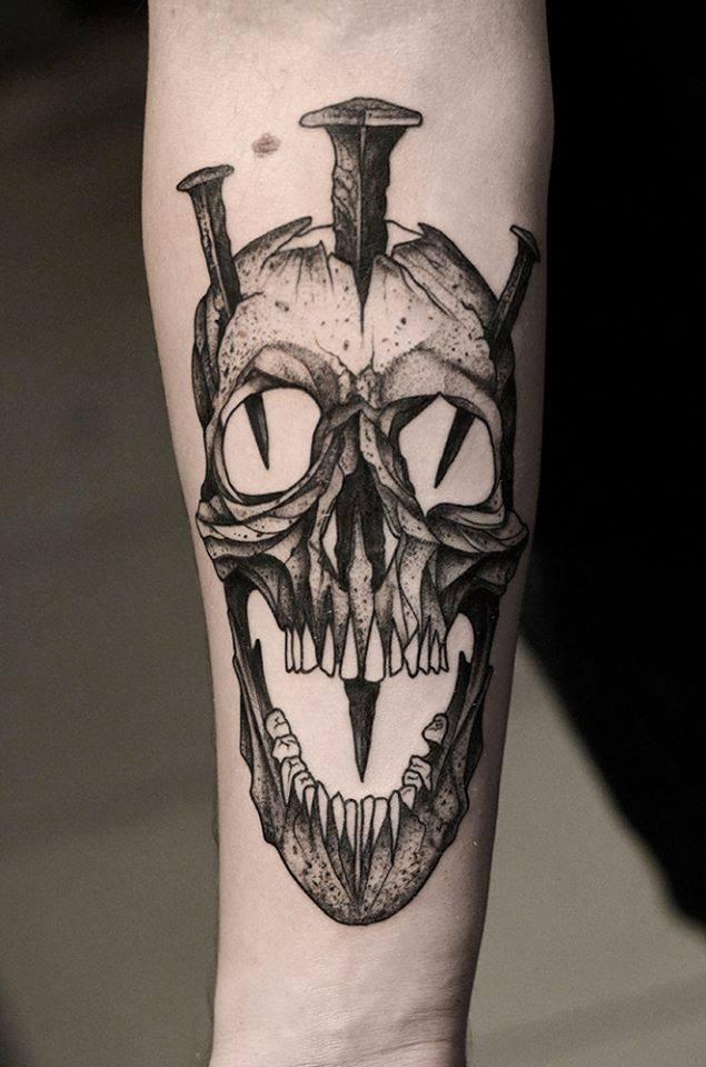 Black ink skull with nails forearm tattoo by Bartosz Wojda