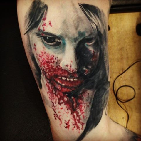 Bloody colored upper arm tattoo of zombie woman face