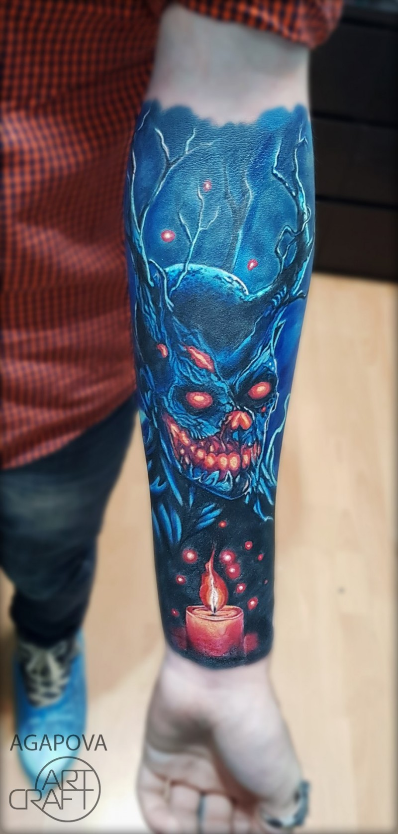 Blue demon tattoo on forearm