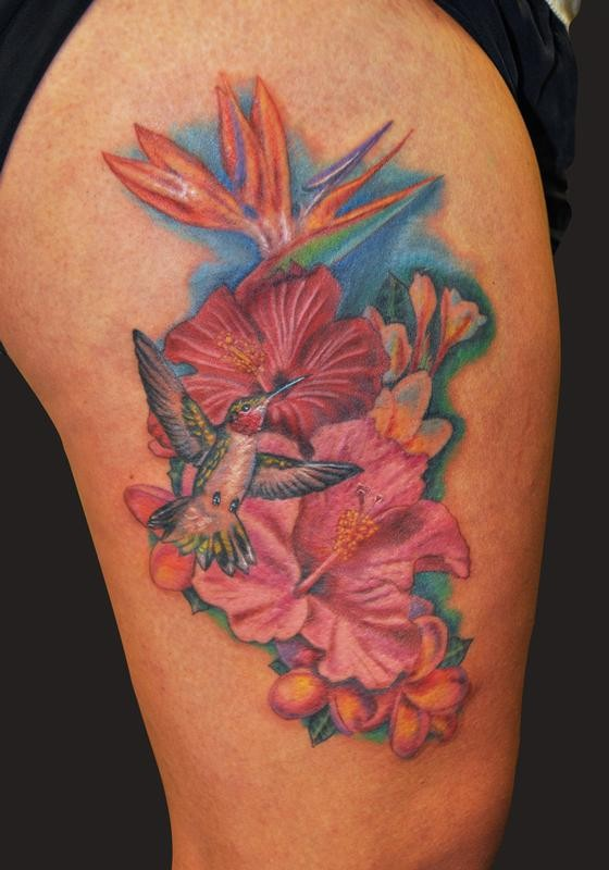 Bright-colored hawaiian flowers and bird tattoo on thigh